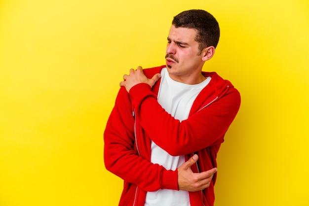Giovane uomo caucasico freddo isolato sulla parete gialla che ha un dolore alla spalla