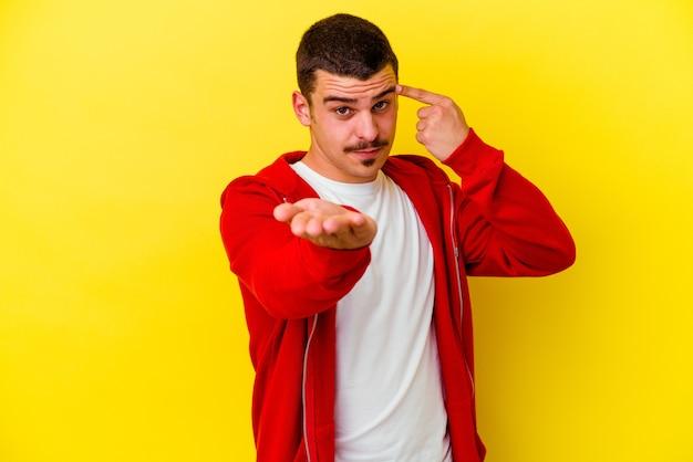Giovane uomo caucasico freddo isolato sulla parete gialla che tiene e che mostra un prodotto a portata di mano.