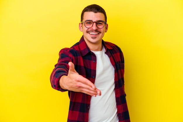 Giovane uomo caucasico freddo sulla mano di allungamento gialla nel gesto di saluto.