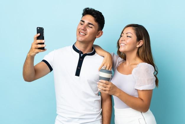 Giovani coppie caucasiche sull'azzurro che fanno un selfie con il cellulare