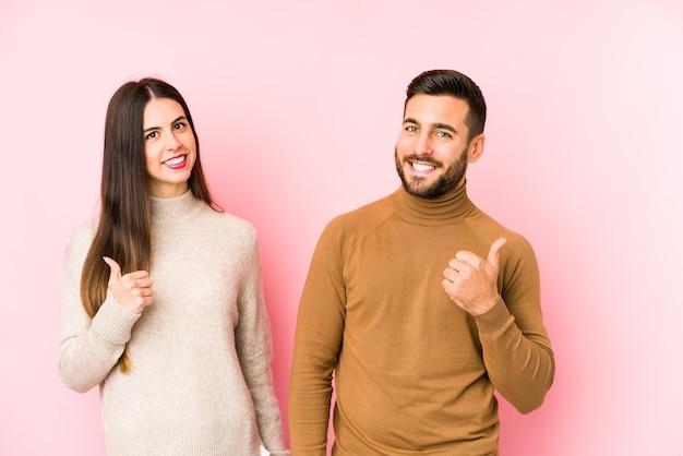 Giovani coppie caucasiche isolate sorridendo e alzando il pollice