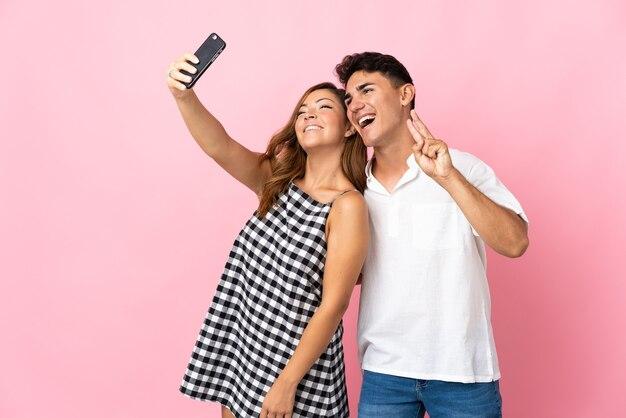 Giovani coppie caucasiche sul rosa che fanno un selfie con il cellulare