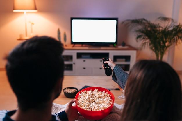 Giovani coppie caucasiche che si siedono su un divano mentre si accende la televisione mangiando popcorn in blocco. copia spazio