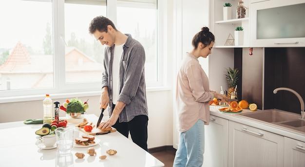 Giovani coppie caucasiche affettare frutta in cucina e preparare la colazione insieme