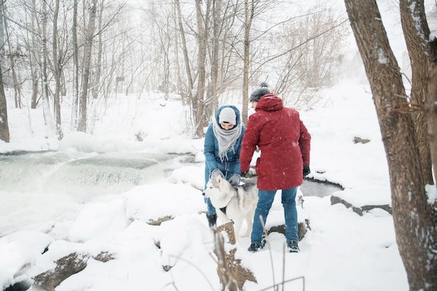 Giovane coppia indoeuropea in piedi con siberian husky in inverno.