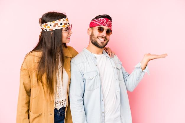 Giovani coppie caucasiche che indossano un festival di musica vestiti isolati mostrando uno spazio di copia su un palmo e tenendo un'altra mano sulla vita.