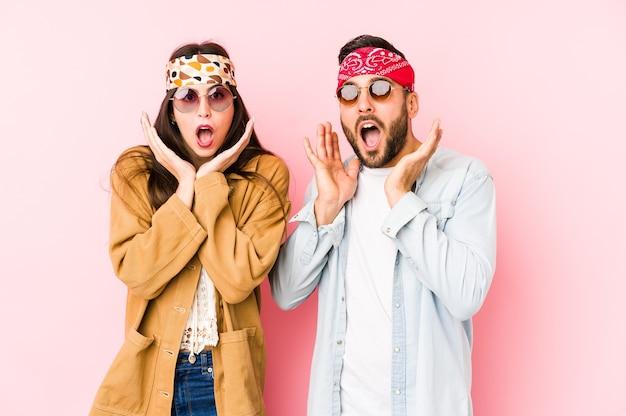 Giovani coppie caucasiche che indossano un festival di musica vestiti isolati sorpresi e scioccati.