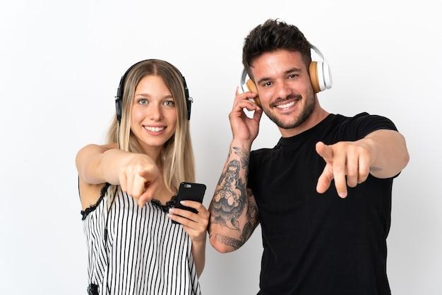 Giovani coppie caucasiche sulla musica d'ascolto bianca e indicando la parte anteriore