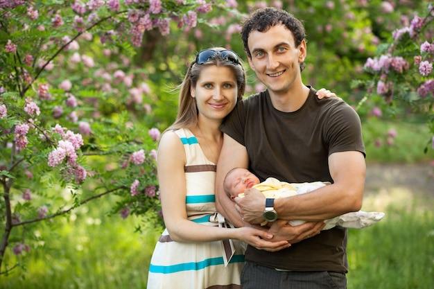 Giovani coppie caucasiche con figlio neonato all'aperto in primavera