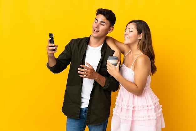 Giovani coppie caucasiche su giallo facendo un selfie con il cellulare