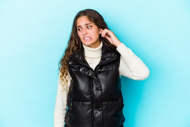 La giovane donna caucasica dei capelli ricci ha isolato le orecchie della copertura con le mani.