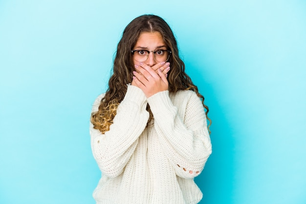 La giovane donna caucasica dei capelli ricci ha isolato la bocca della copertura con le mani che sembrano preoccupate.