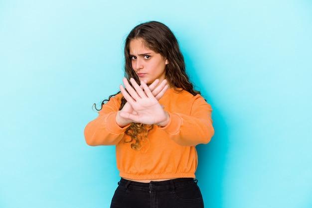 Giovane donna caucasica dei capelli ricci isolata facendo un gesto di rifiuto