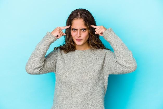 La giovane donna caucasica dei capelli ricci isolata si è concentrata su un compito, mantenendo gli indici che puntano la testa.