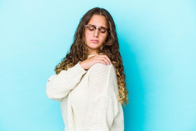 Giovane donna caucasica dei capelli ricci isolata avendo un dolore alla spalla.