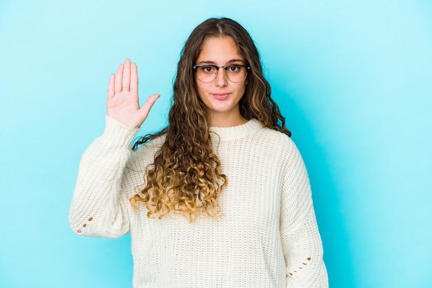 La giovane donna caucasica dei capelli ricci ha isolato sorridente allegro che mostra il numero cinque con le dita.