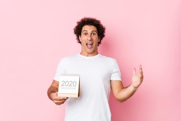 Giovane uomo riccio caucasico che tiene un calendario 2020 che celebra una vittoria o un successo