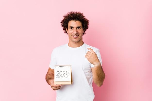 Giovane uomo riccio caucasico che tiene un calendario 2020 che indica con il dito come se l'invito si avvicini.