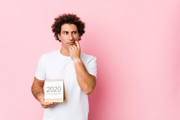 Il giovane uomo riccio caucasico che tiene un calendario 2020 si è disteso pensando a qualcosa che esamina uno spazio della copia.