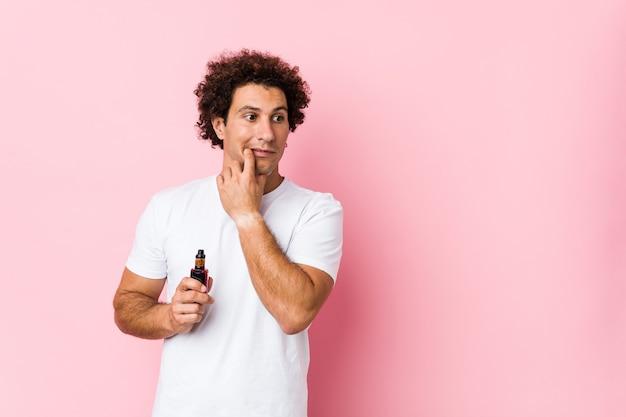 Il giovane uomo riccio caucasico che tiene un vape rilassato pensando a qualcosa guardando uno spazio di copia.
