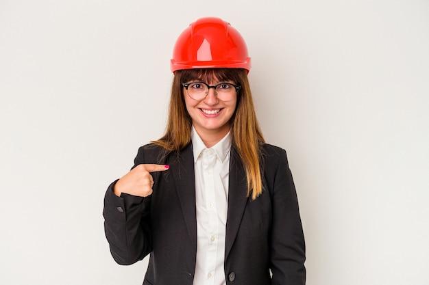 Giovane donna architetto curvy caucasica isolata su sfondo bianco persona che punta a mano a uno spazio copia camicia, orgoglioso e fiducioso