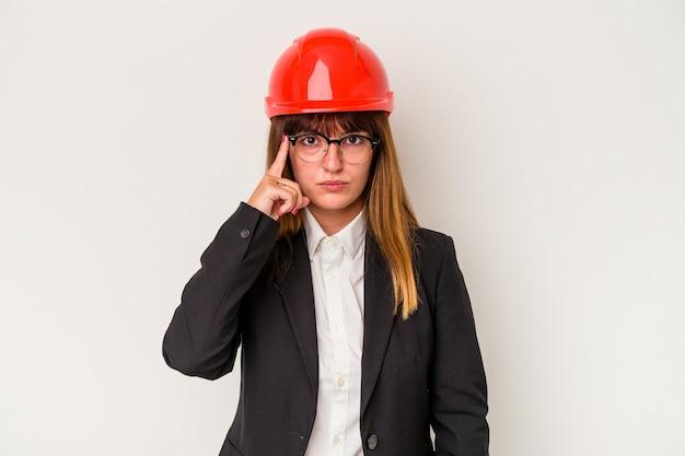 Giovane donna caucasica architetto curvy isolata su sfondo bianco che indica tempio con il dito, pensando, focalizzato su un compito.