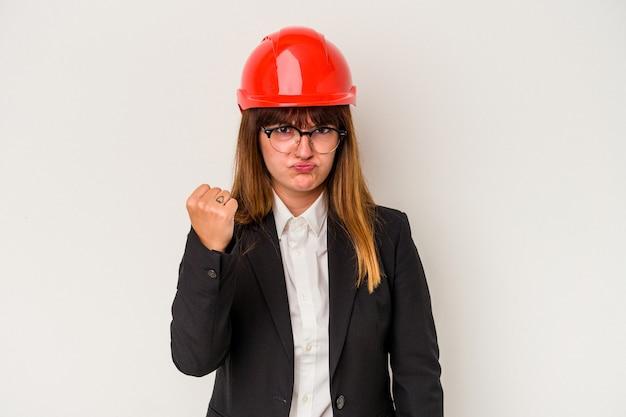 Giovane donna curvy caucasica dell'architetto isolata su fondo bianco che mostra pugno alla macchina fotografica, espressione facciale aggressiva.