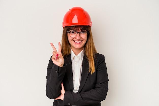 Giovane donna curvy caucasica dell'architetto isolata su fondo bianco che mostra il numero due con le dita.