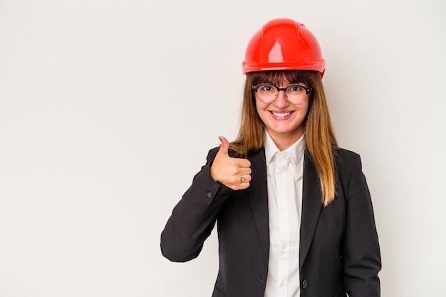 Giovane donna curvy caucasica dell'architetto isolata su fondo bianco che sorride e che alza pollice su