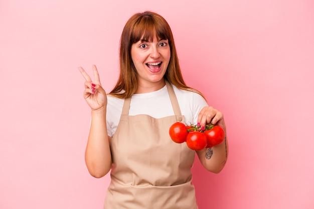 Giovane donna curvy caucasica che cucina a casa tenendo i pomodori isolati su sfondo rosa gioiosa e spensierata che mostra un simbolo di pace con le dita.