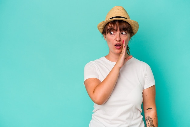 La giovane donna formosa caucasica isolata su sfondo blu sta dicendo una notizia segreta di frenata calda e sta guardando da parte