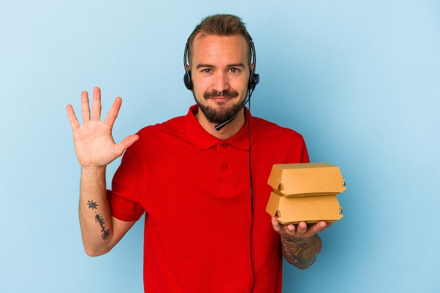 Giovane fattorino caucasico con tatuaggi che tengono hamburger isolati su sfondo blu sorridente allegro che mostra il numero cinque con le dita.