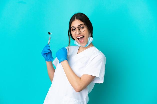Giovane donna caucasica del dentista che tiene gli strumenti isolati su fondo blu che celebra una vittoria