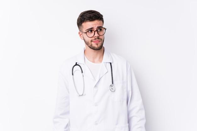 Giovane uomo caucasico medico isolato confuso, si sente dubbioso e insicuro.