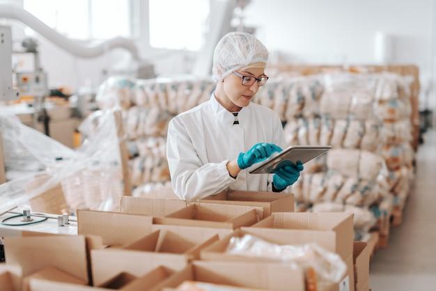 Giovane impiegato caucasico in uniforme sterile facendo uso della compressa per la logistica. interno di fabbrica alimentare.