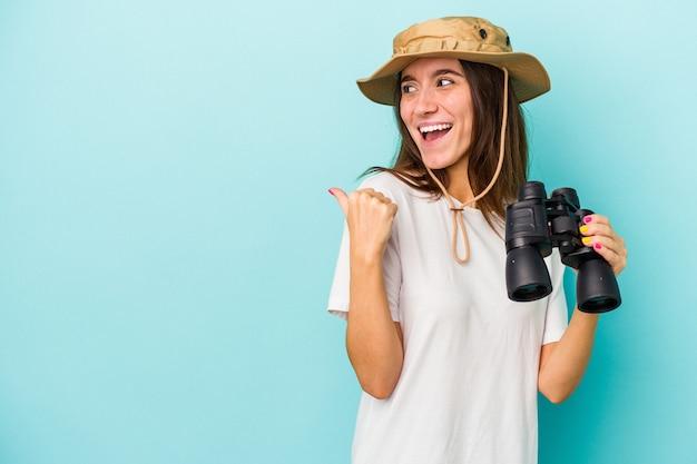 La giovane donna caucasica dell'esploratore che tiene il binocolo isolato su sfondo blu indica con il dito del pollice lontano, ridendo e spensierato.