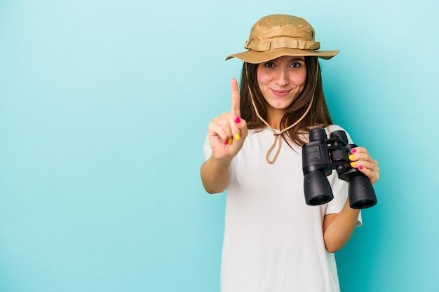 Giovane donna caucasica dell'esploratore che tiene il binocolo isolato su sfondo blu che mostra il numero uno con il dito.