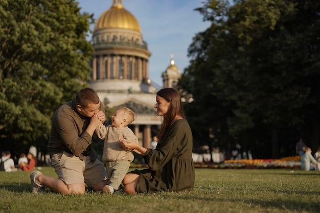 Giovane famiglia caucasica padre madre e figlio piccolo seduto sull'erba di fronte a san isaac cat