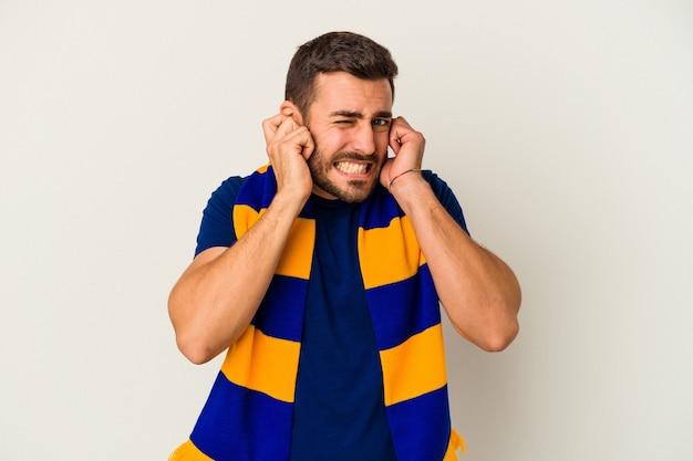 Giovane fan caucasico di una squadra di calcio isolata su sfondo bianco che copre le orecchie con le mani.