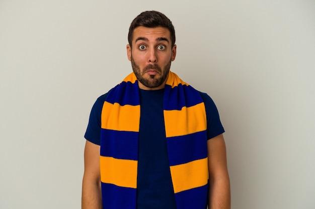 Giovane tifoso indoeuropeo di una squadra di calcio isolata su sfondo bianco alza le spalle e gli occhi aperti confusi.