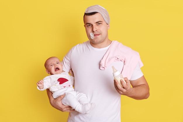 Giovane padre caucasico che dà latte alla sua bambina, ragazza neonato che piange nelle mani di papà, ragazzo stanco con succhietto per bambini in bocca, in piedi isolato sopra il muro giallo.