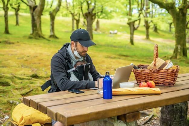 Un giovane padre caucasico telelavoro seduto a un tavolo da picnic con il computer nel bosco