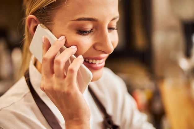 Giovane barista caucasica in uniforme che parla al cellulare