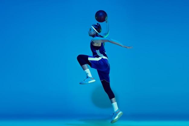 Giovane giocatore di basket femminile caucasico isolato su sfondo blu studio in luce al neon