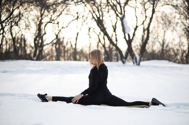 Giovane bionda femmina caucasica in leggings esercizio di stretching seduto su una corda all'aria aperta nella foresta innevata. in forma e stile di vita sportivo.