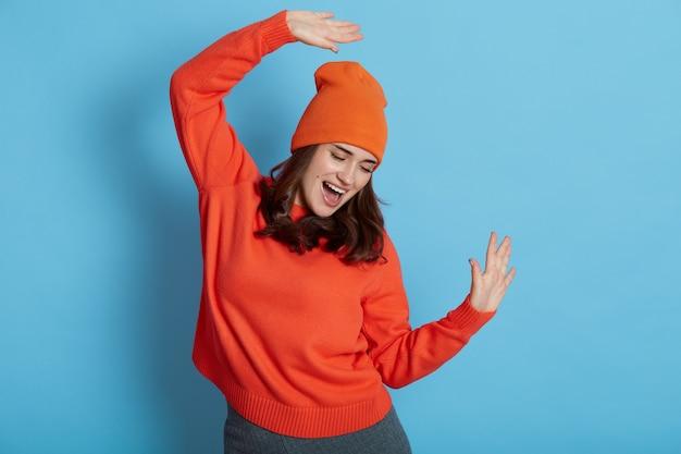 La giovane femmina caucasica veste il maglione e il cappello che ballano allegramente, celebrando il suo successo, ha una grande notizia, alza le braccia e tiene la bocca aperta, isolata sul muro blu.