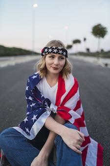 Giovane donna caucasica seduta sulla strada asfaltata con la bandiera degli stati uniti sulle spalle