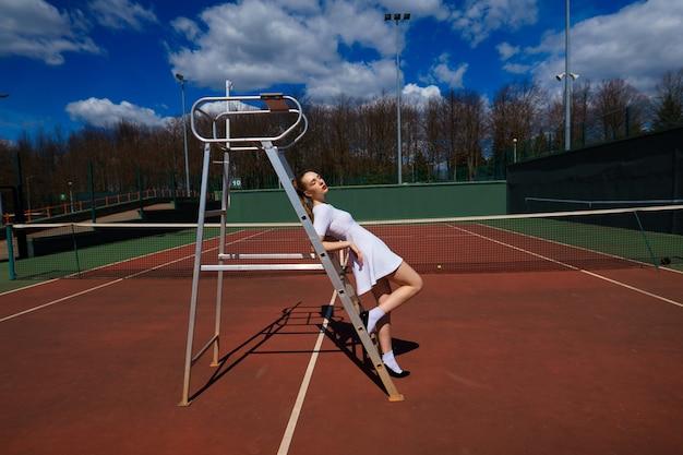 Il giovane giocatore di tennis femminile caucasico sulla corte rimane vicino alla scala dell'arbitro