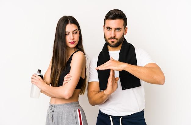 Giovani coppie caucasiche di forma fisica che mostrano un gesto di timeout.