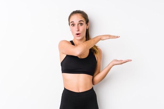 Giovane donna caucasica di forma fisica che posa in uno spazio bianco scioccata e stupita che tiene uno spazio della copia tra le mani.